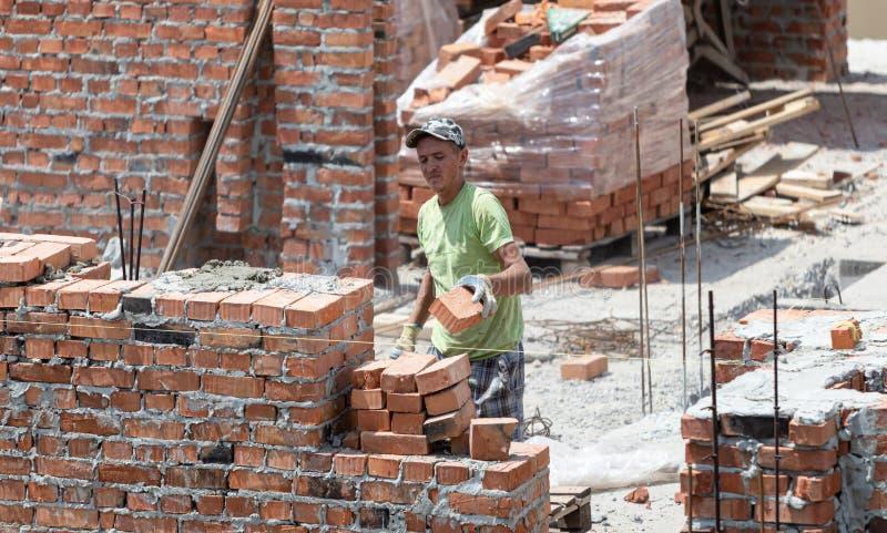 Οι επαγγελματικοί βιοτέχνες χτίζουν ένα σπίτι τούβλου στοκ εικόνες