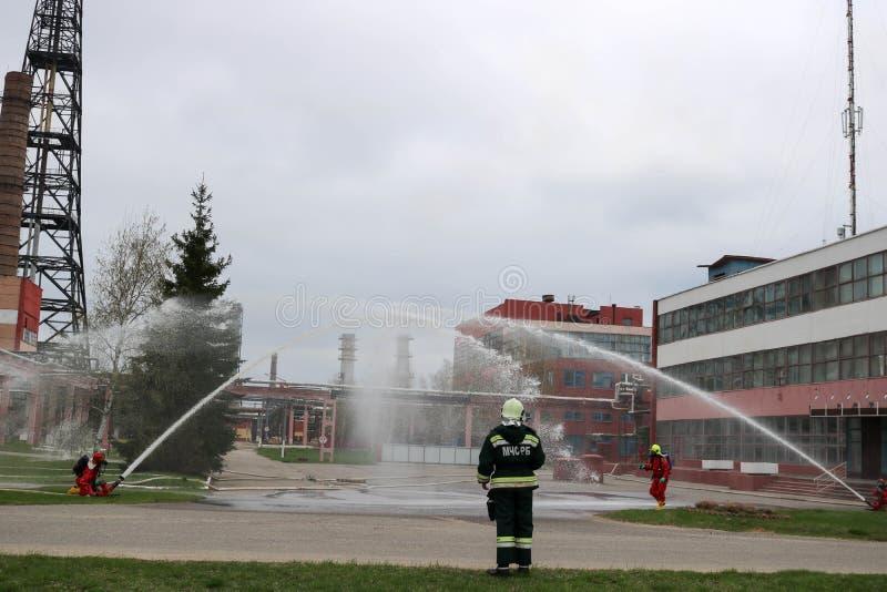 Οι επαγγελματικοί πυροσβέστες στα πορτοκαλιά πυρίμαχα κοστούμια στα άσπρα κράνη με τις μάσκες αερίου εξετάζουν τις μάνικες πυρκαγ στοκ εικόνες με δικαίωμα ελεύθερης χρήσης