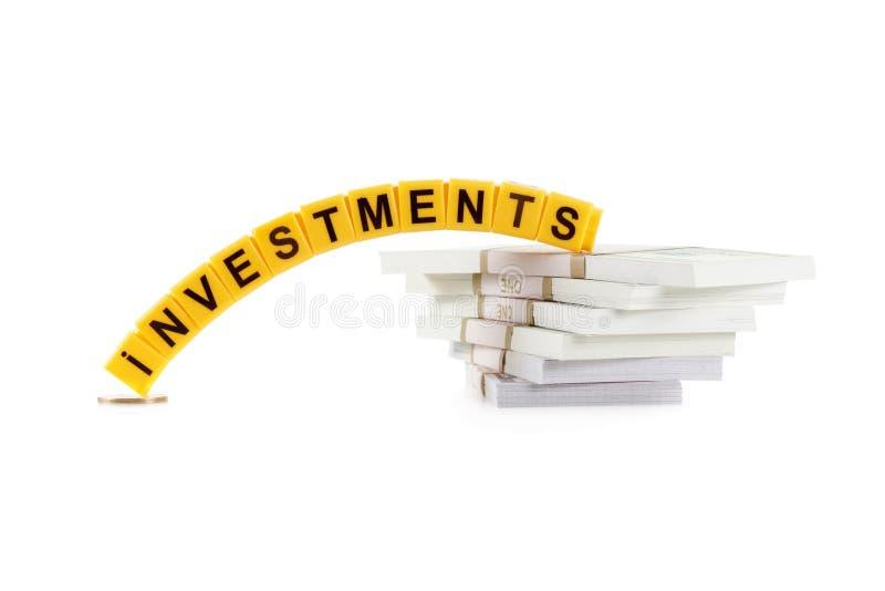 Οι επενδύσεις έννοιας, λέξη έκαναν με επιστολή, σωρός των λογαριασμών δολαρίων στοκ φωτογραφίες