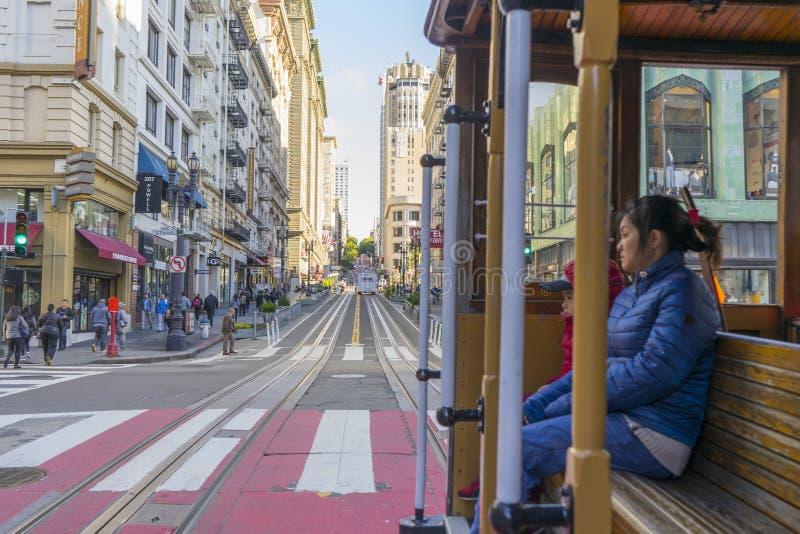 Οι επιβάτες απολαμβάνουν έναν γύρο σε ένα τελεφερίκ στο Σαν Φρανσίσκο, Καλιφόρνια στοκ εικόνα με δικαίωμα ελεύθερης χρήσης
