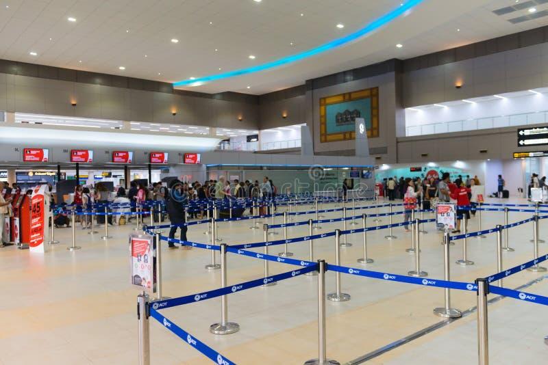 Οι επιβάτες περιμένουν στη σειρά επάνω στους μετρητές επικόλλησης ετικέτας μέσα Don Mueang στοκ εικόνες