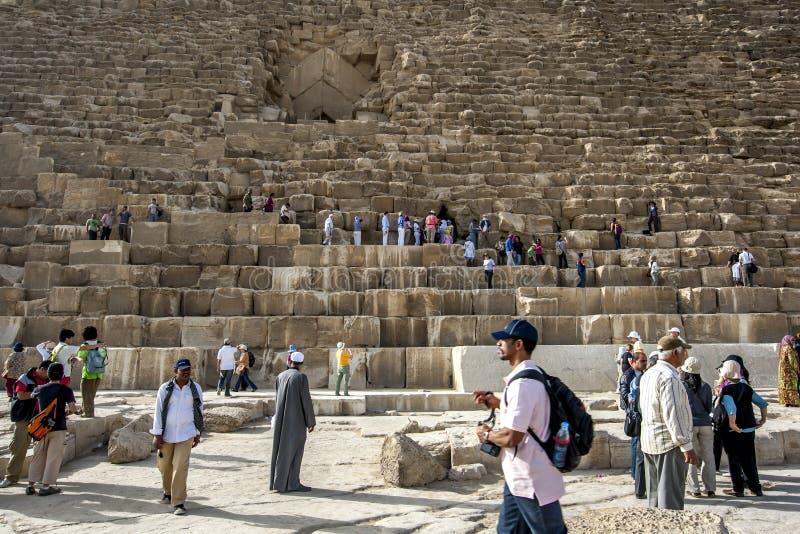 Οι επισκέπτες σε Giza στο Κάιρο στην Αίγυπτο αναρριχούνται πέρα από την πυραμίδα Khufu στοκ εικόνες