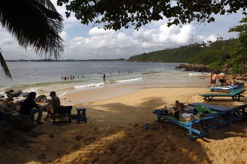 Οι επισκέπτες χαλαρώνουν κάτω από τα δέντρα στην παραλία ζουγκλών σε Unawatuna στη νότια παράλια της Σρι Λάνκα στοκ φωτογραφίες με δικαίωμα ελεύθερης χρήσης