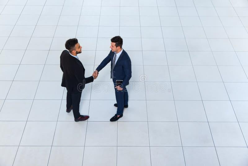 Οι επιχειρηματίες δίνουν στο κούνημα την ευπρόσδεκτη χειρονομία τοπ άποψη γωνίας, δύο επιχειρησιακά άτομα κάνουν τη χειραψία διαπ στοκ φωτογραφία