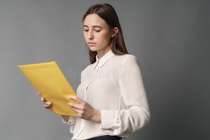 Οι επιχειρηματίες κρατούν τα έγγραφα στο χέρι της ένας Απομονωμένος στην γκρίζα ανασκόπηση στοκ φωτογραφία