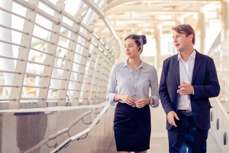 Οι επιχειρηματίες μιλούν σε γυναίκες επιχειρηματίες ενώ περπατούν και ξεκουράζονται στο Skywalk, στην Teamwork, στην ομάδα των συ στοκ φωτογραφία με δικαίωμα ελεύθερης χρήσης