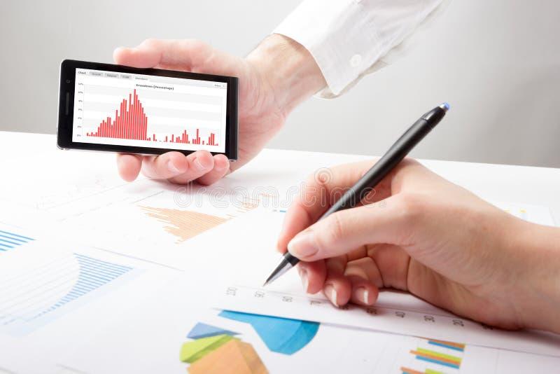 Οι επιχειρηματίες σε μια συνεδρίαση που αναλύει τις οικονομικές εκθέσεις συζητούν στοκ φωτογραφία με δικαίωμα ελεύθερης χρήσης