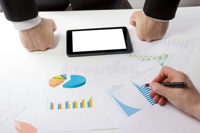 Οι επιχειρηματίες σε μια συνεδρίαση που αναλύει τις οικονομικές εκθέσεις συζητούν στοκ εικόνα