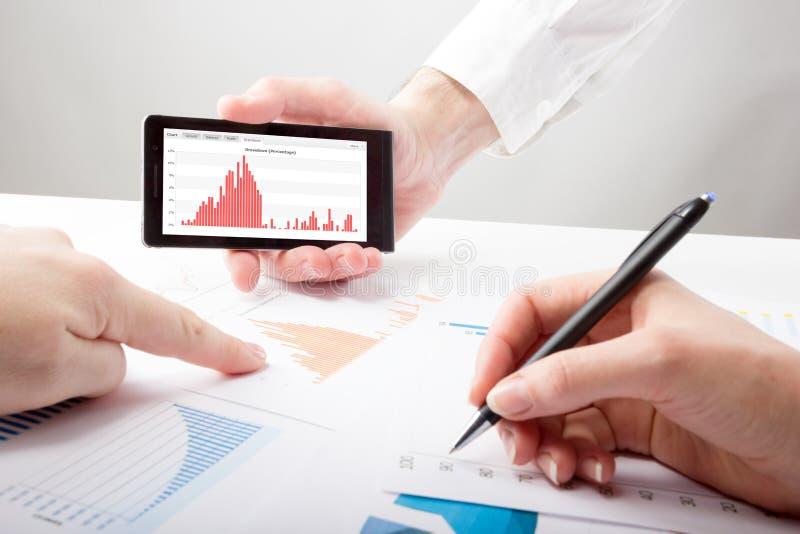 Οι επιχειρηματίες σε μια συνεδρίαση που αναλύει τις οικονομικές εκθέσεις συζητούν στοκ εικόνες με δικαίωμα ελεύθερης χρήσης