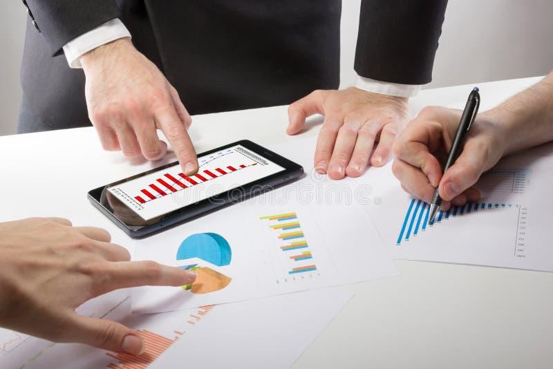 Οι επιχειρηματίες σε μια συνεδρίαση που αναλύει τις οικονομικές εκθέσεις συζητούν στοκ εικόνες