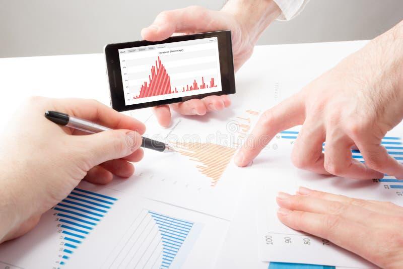 Οι επιχειρηματίες σε μια συνεδρίαση που αναλύει τις οικονομικές εκθέσεις συζητούν στοκ φωτογραφία
