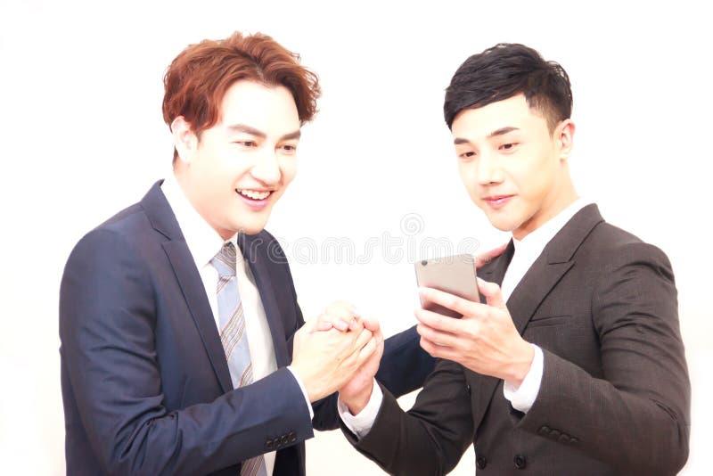Οι επιχειρηματίες συγχαίρουν ευτυχώς ο ένας στον άλλο κατά την εξέταση τη διαπραγμάτευση οδηγούν στο έξυπνο τηλέφωνο Εννοιολογική στοκ εικόνες