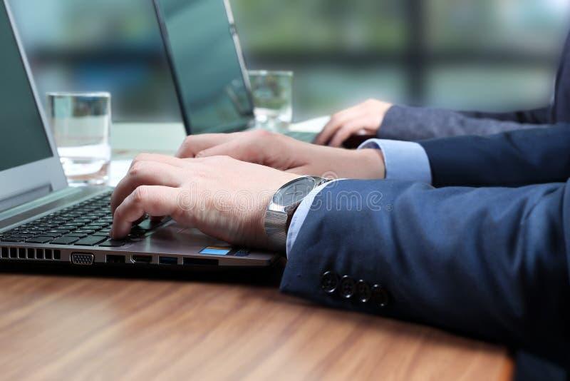 Οι επιχειρησιακοί εργαζόμενοι στα γραφεία με ένα lap-top πολυάσχολο σε δημιουργικό στοκ φωτογραφία με δικαίωμα ελεύθερης χρήσης