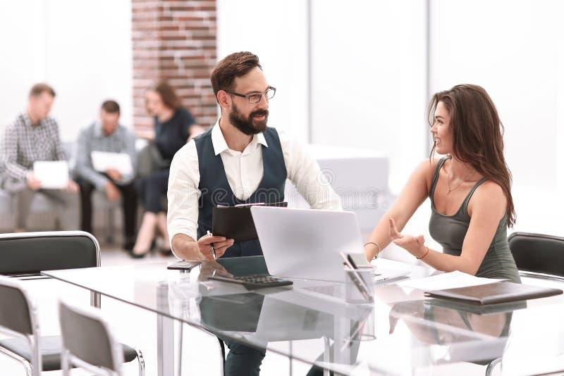 Οι επιχειρησιακοί συνάδελφοι συζητούν τα επιχειρησιακά ζητήματα καθμένος στο γραφείο στοκ φωτογραφίες με δικαίωμα ελεύθερης χρήσης