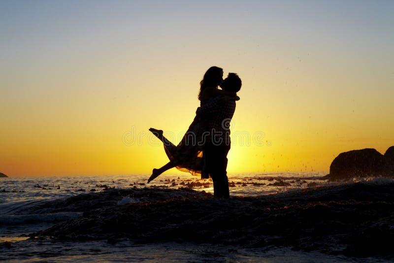 Οι εραστές αγκαλιάζουν σκιαγραφημένος από ένα ηλιοβασίλεμα στοκ φωτογραφία