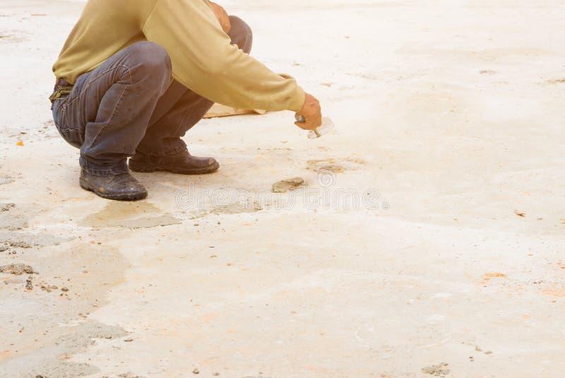 οι εργάτες οικοδομών επικονίαζαν το πάτωμα επισκευής στον εργασιακό χώρο χτίζουν ένα σπίτι στοκ φωτογραφία