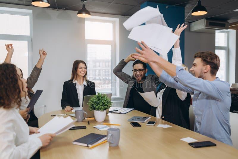 Οι εργαζόμενοι γραφείων γιορτάζουν την επιχειρησιακή επιτυχία και ρίχνουν επάνω στα έγγραφα και τα έγγραφα στοκ εικόνες