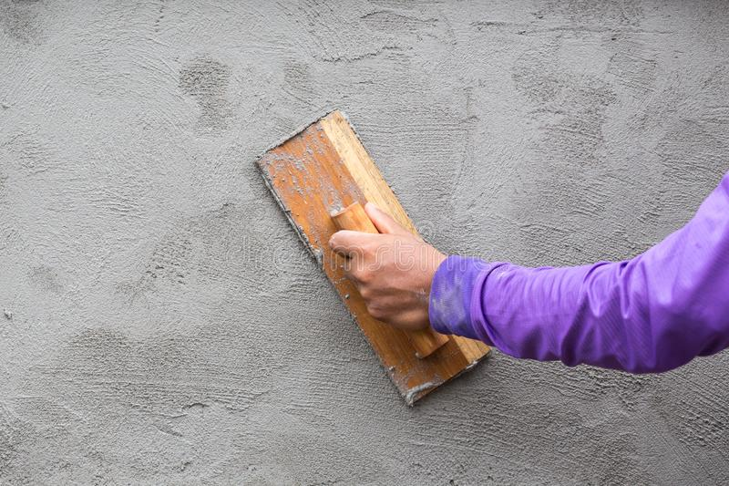 Οι εργαζόμενοι είναι επικονιασμένοι τοίχοι Γυψαδόρος χεριών στην εργασία Εφαρμογή του ασβεστοκονιάματος στον τοίχο στοκ φωτογραφίες