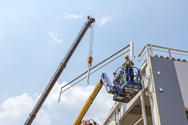 Οι εργαζόμενοι είναι υψηλοί επάνω στη συλλεκτική μηχανή κερασιών στο εργοτάξιο στοκ φωτογραφία