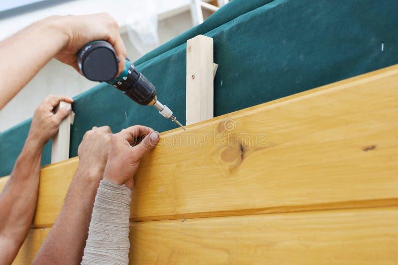 Οι εργαζόμενοι εγκαθιστούν ένα φυσικό καφετί ξύλο πεύκων στο καινούργιο σπίτι κάτω από την κατασκευή στοκ εικόνα με δικαίωμα ελεύθερης χρήσης