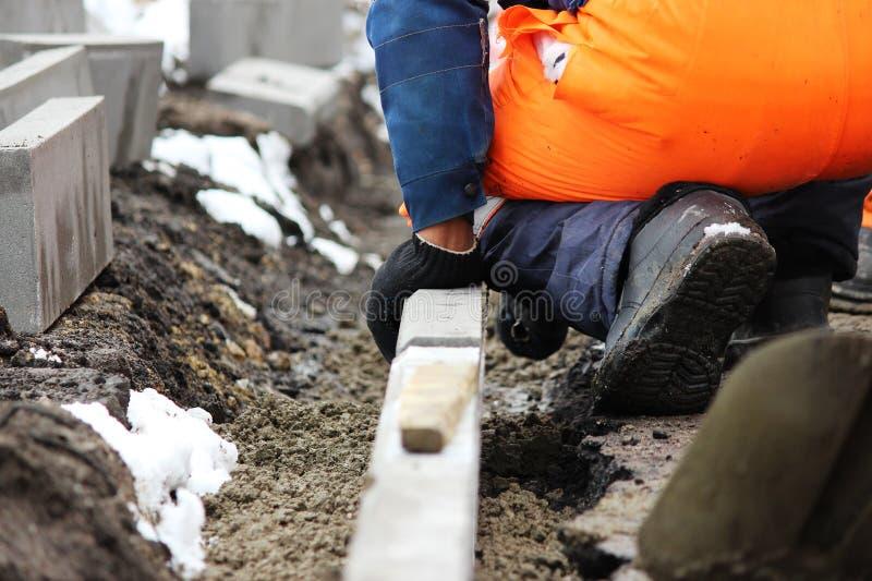 Οι εργαζόμενοι λιθοδόμοι επισκευάζουν το πεζοδρόμιο, εγκαθιστούν τις συγκρατήσεις πρίν ασφαλτώνουν για το δρόμο στοκ φωτογραφίες με δικαίωμα ελεύθερης χρήσης