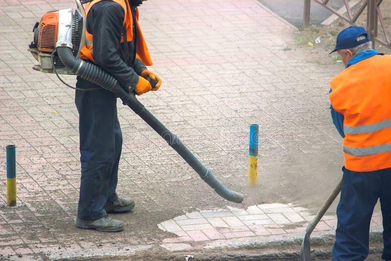 οι εργαζόμενοι κοινωνικής υπηρεσίας καθαρίζουν το πεζοδρόμιο στοκ εικόνες