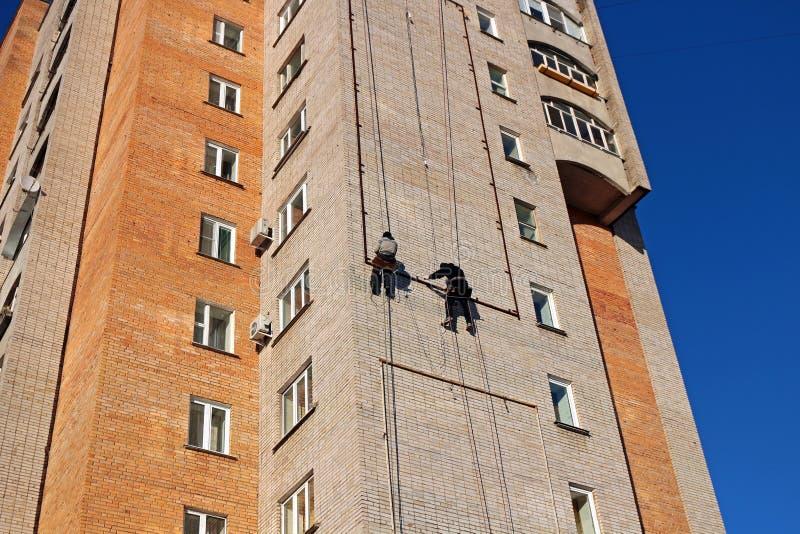 Οι εργαζόμενοι κρεμούν τη διαφήμιση σε ένα κτήριο στοκ φωτογραφία με δικαίωμα ελεύθερης χρήσης