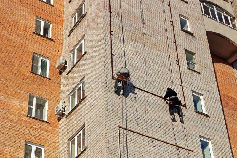 Οι εργαζόμενοι κρεμούν τη διαφήμιση σε ένα κτήριο στοκ εικόνα