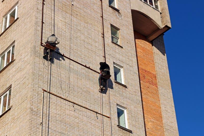 Οι εργαζόμενοι κρεμούν τη διαφήμιση σε ένα κτήριο στοκ εικόνες