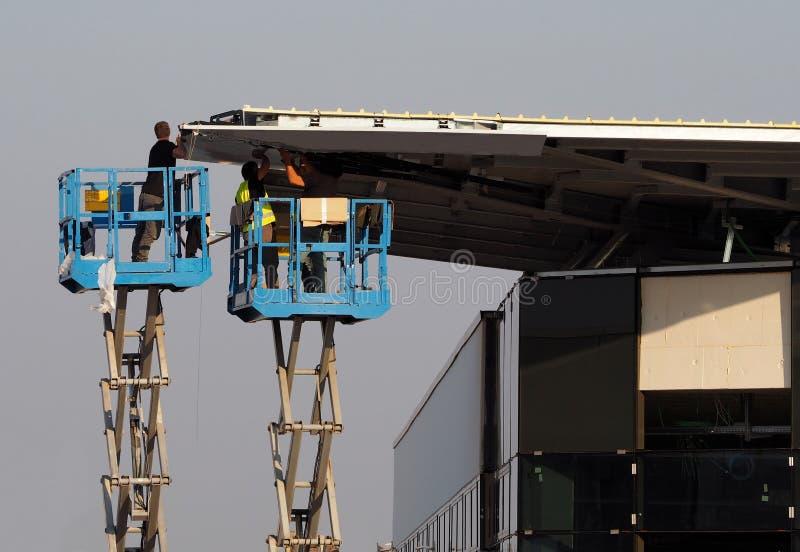 Οι εργαζόμενοι σε δύο συλλεκτικές μηχανές κερασιών, ανελκυστήρες ψαλιδιού, τελειώνουν την πρόσοψη ενός νέου κτηρίου χτίζουν ακριβ στοκ εικόνα με δικαίωμα ελεύθερης χρήσης