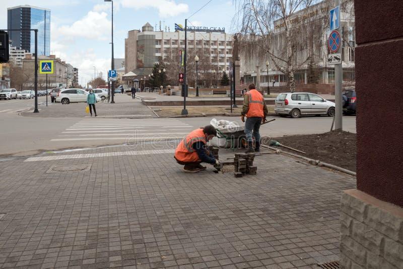 Οι εργαζόμενοι στις φωτεινές προστατευτικές φανέλλες επισκευάζουν τις πλάκες επίστρωσης μπροστά από ένα για τους πεζούς πέρασμα σ στοκ εικόνες