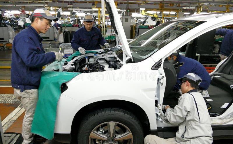 Οι εργαζόμενοι συγκεντρώνουν ένα αυτοκίνητο στη γραμμή συνελεύσεων στο εργοστάσιο αυτοκινήτων στοκ εικόνες