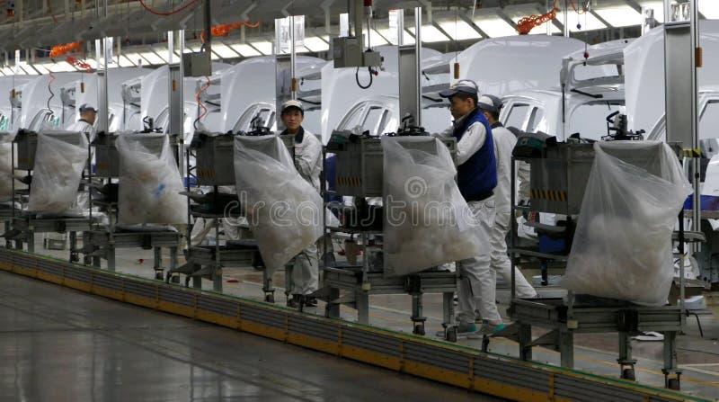 Οι εργαζόμενοι συγκεντρώνουν ένα αυτοκίνητο στη γραμμή συνελεύσεων στο εργοστάσιο αυτοκινήτων στοκ φωτογραφίες