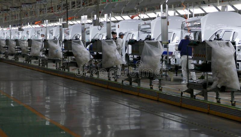Οι εργαζόμενοι συγκεντρώνουν ένα αυτοκίνητο στη γραμμή συνελεύσεων στο εργοστάσιο αυτοκινήτων στοκ φωτογραφία με δικαίωμα ελεύθερης χρήσης