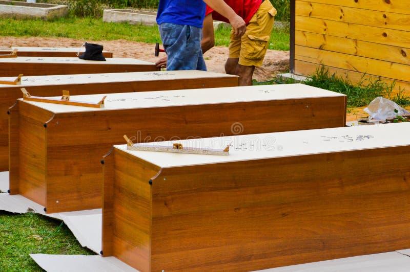 Οι εργαζόμενοι συγκεντρώνουν τα νέα ξύλινα έπιπλα γραφείων στην οδό στοκ εικόνα