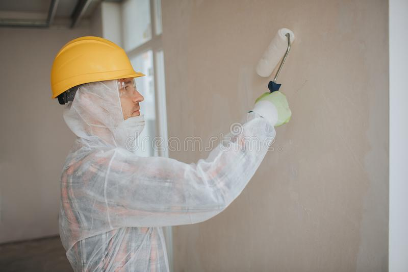 Οι εργασίες οικοδόμων στο εργοτάξιο οικοδομής Εργαζόμενος με έναν κύλινδρο χρωμάτων Φορά ένα προστατευτικές κοστούμι και μια μάσκ στοκ εικόνες