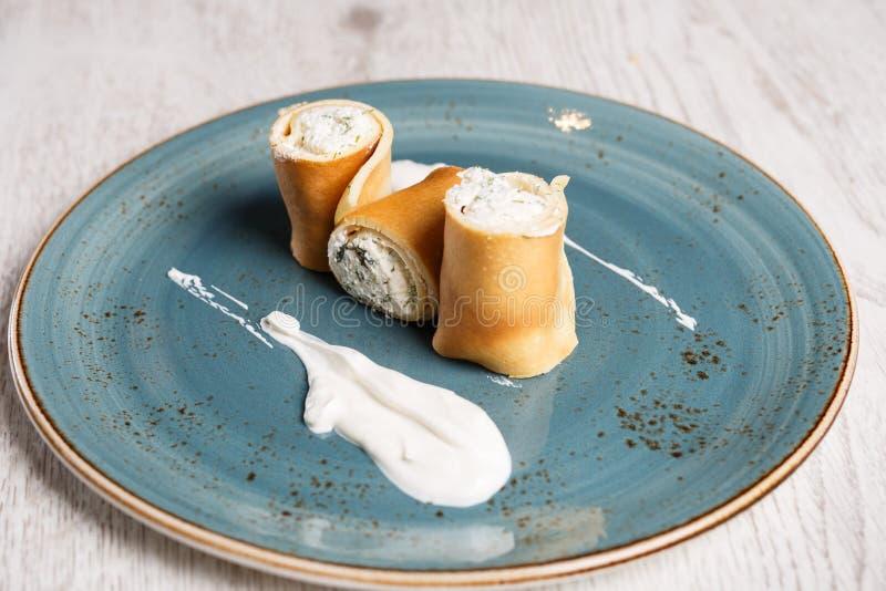 Οι ευρωπαϊκές τηγανίτες, crepes, με το τυρί κρέμας και την ξινή κρέμα στοκ φωτογραφία