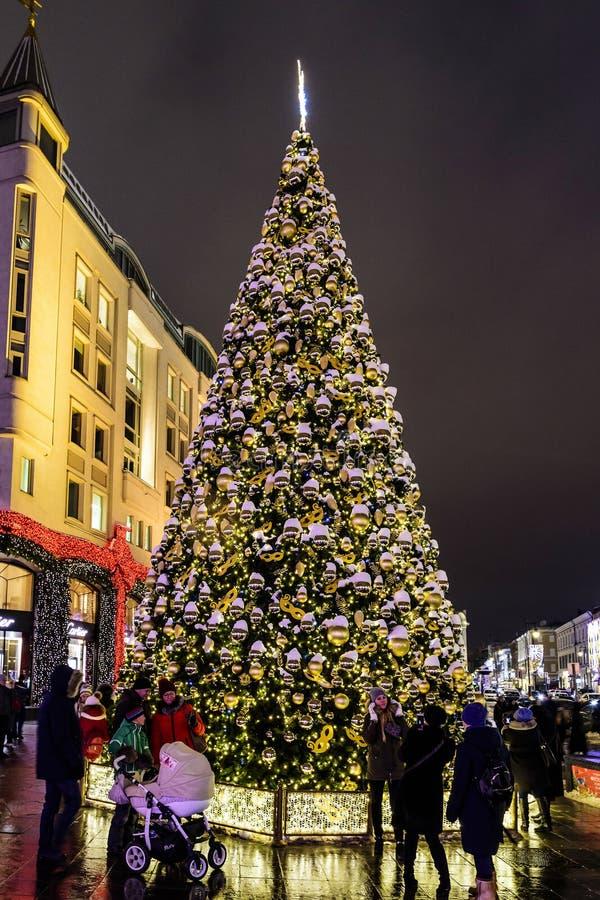 Οι ευτυχείς άνθρωποι κοντά σε ένα όμορφο χριστουγεννιάτικο δέντρο με τα παιχνίδια κάνουν τις φωτογραφίες σε ένα χειμερινό βράδυ Μ στοκ φωτογραφίες με δικαίωμα ελεύθερης χρήσης