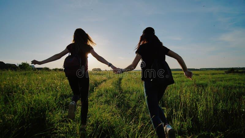 Οι ευτυχείς ανώτεροι μαθητές φεύγουν και πετούν τα χαρτοφυλάκιά τους ενάντια στο ηλιοβασίλεμα Ευτυχείς τελειώνοντας σχολικές ημέρ στοκ εικόνες