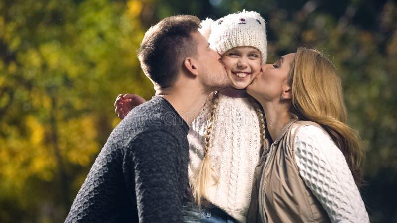 Οι ευτυχείς γονείς φιλούν την εύθυμη κόρη στο πάρκο φθινοπώρου, πλούσια οικογένεια, ευημερία στοκ φωτογραφίες