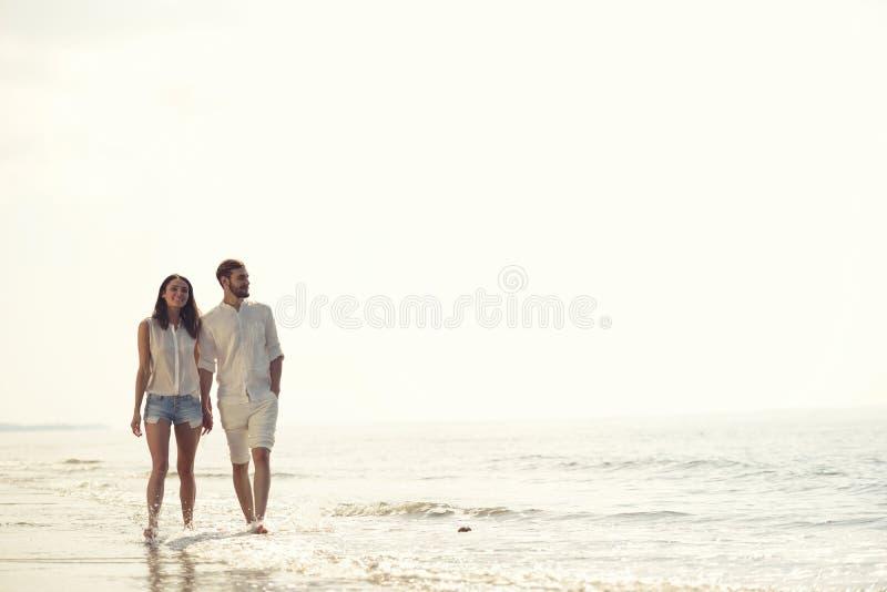 Οι ευτυχείς διακοπές παραλιών διασκέδασης συνδέουν το περπάτημα μαζί να γελάσουν έχοντας τη διασκέδαση στον προορισμό ταξιδιού στοκ φωτογραφία