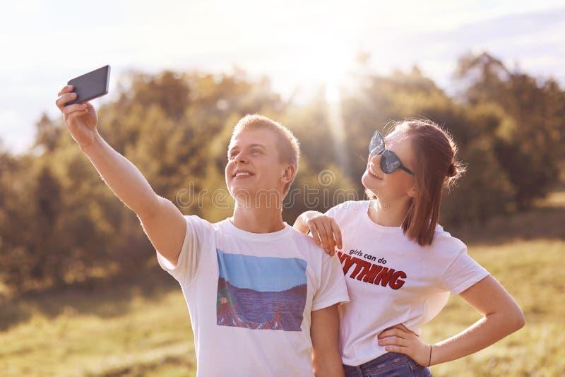 Οι ευτυχείς καλύτεροι φίλοι θέτουν για την παραγωγή selfie, κρατούν το έξυπνο τηλέφωνο, χαμογελούν ήπια, απολαμβάνουν το χρόνο αν στοκ εικόνα