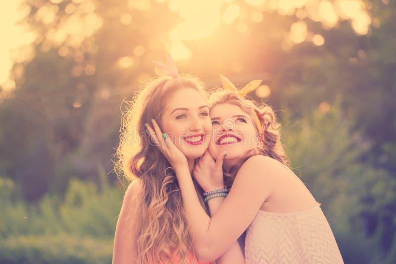 Οι ευτυχείς καλύτερες φίλες αγκαλιάζουν Ηλιοβασίλεμα στοκ φωτογραφία