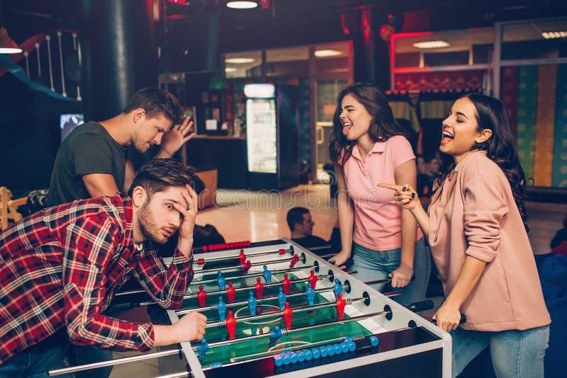 Οι ευτυχείς νέες γυναίκες εξετάζουν τους άνδρες και συρρικνώνονται Κερδίζουν το παιχνίδι Οι τύποι το έχασαν  Οι νέοι στέκονται στ στοκ φωτογραφία