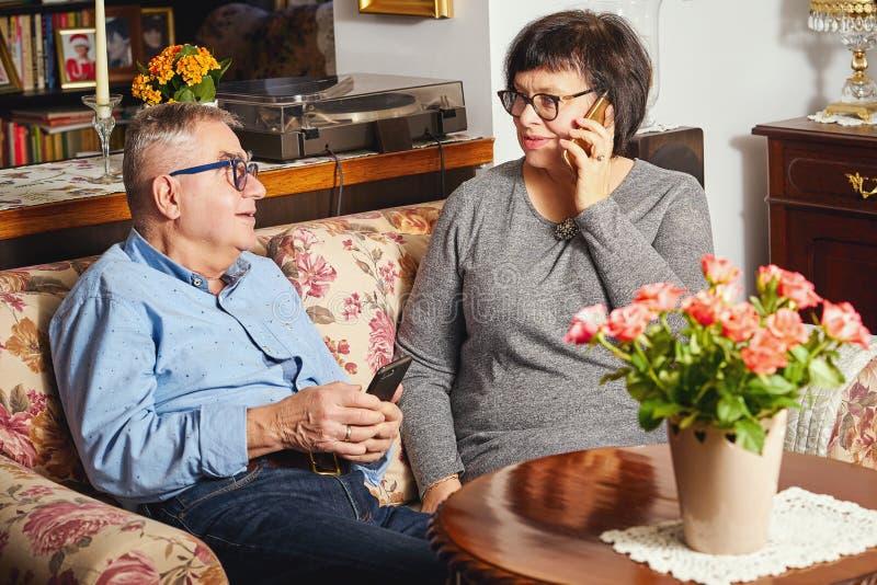 Οι ευτυχείς πρεσβύτεροι συνδέουν τη συνεδρίαση στον καναπέ μιλώντας γυναικών στο τηλέφωνο στοκ εικόνες