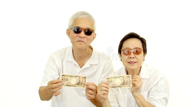 Οι ευτυχείς πλούσιοι δροσίζουν τον ασιατικό πρεσβύτερο που παρουσιάζει στα χρήματα μετρητών ιαπωνικά γεν στοκ εικόνα με δικαίωμα ελεύθερης χρήσης