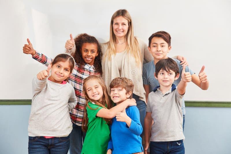 Οι ευτυχείς σπουδαστές κρατούν τους αντίχειρές τους επάνω στοκ φωτογραφία