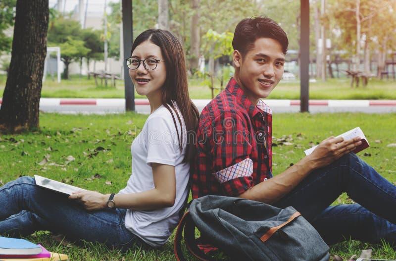 Οι ευτυχείς σπουδαστές συνδέουν να καθίσουν μαζί στο πανεπιστήμιο στοκ εικόνες