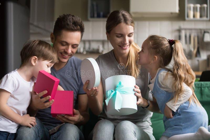 Οι ευτυχείς συγκινημένοι γονείς που ανοίγουν τα κιβώτια δώρων με παρουσιάζουν από τα παιδιά στοκ φωτογραφία με δικαίωμα ελεύθερης χρήσης