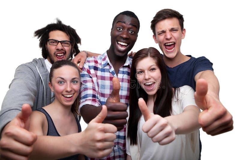 Οι ευτυχείς φίλοι που εμφανίζουν αντίχειρα υπογράφουν επάνω στοκ φωτογραφία
